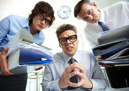 the bookkeeper: Pleading accountant looking at camera being surrounded by his partners holding huge piles of documents Stock Photo