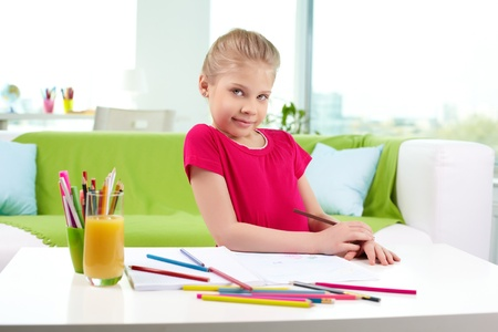 Lovely girl looking at camera while drawing with colorful pencils Stock Photo - 13589744