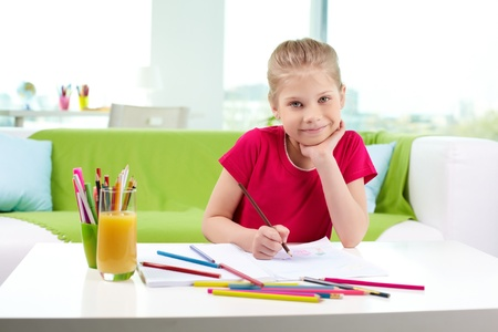 Lovely girl looking at camera while drawing with colorful pencils Stock Photo - 13589742