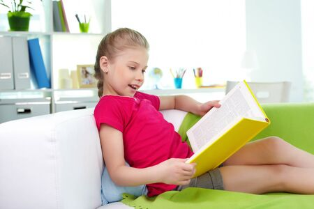 Portrait of lovely girl reading interesting book at home photo