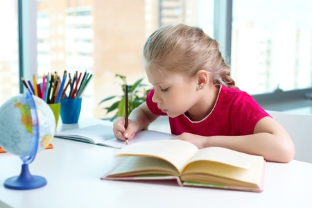 creative writing: Portrait of lovely girl drawing with pencil in copybook