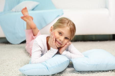 Portrait of lovely girl lying on the floor at home photo