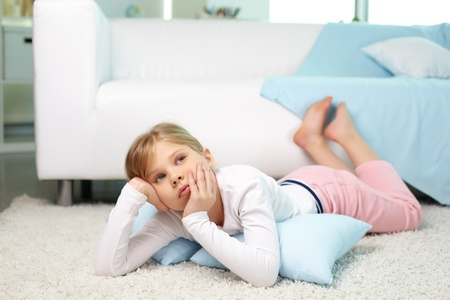 Portrait of pensive girl lying on the floor at home photo