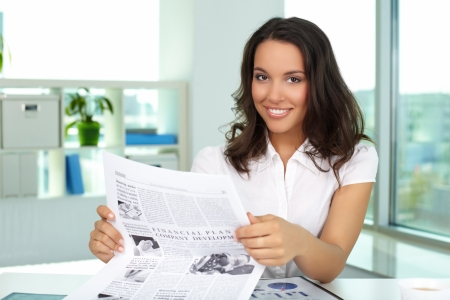 Portrait of a beautiful lady with newspaper looking at camera photo