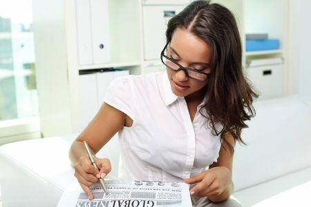 Portrait of a beautiful business lady reading newspaper in office photo