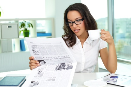 Portrait of a business lady reading newspaper and drinking coffee in the morning photo