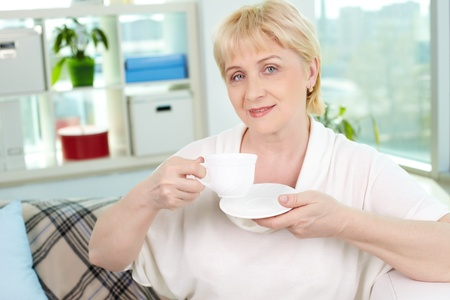 Portrait of friendly aged woman with cup of tea looking at camera Stock Photo - 13631117