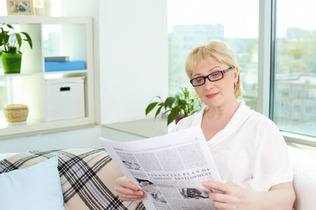 Portrait of aged woman reading newspaper at home photo