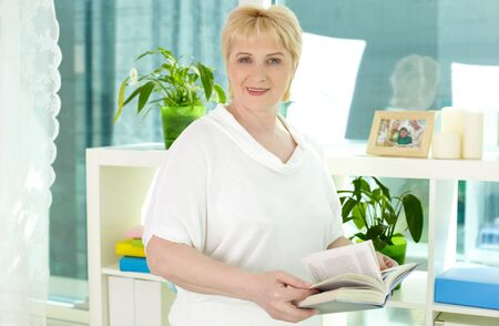 Portrait of mature woman spending leisure at home photo