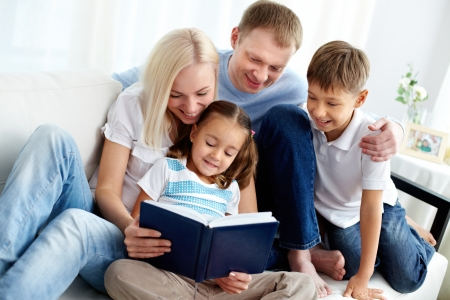 male parent: Portrait of happy family with two children reading book