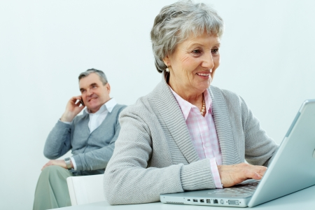 Portrait of senior woman typing with a man speaking on the phone on background  photo