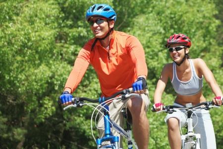 cyclist: Portret van een knappe man op een fiets met zijn vrouw op de achtergrond