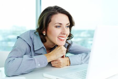 computer user: Smiling business woman looking at the screen of computer