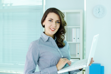 Smiling business woman with laptop looking at camera