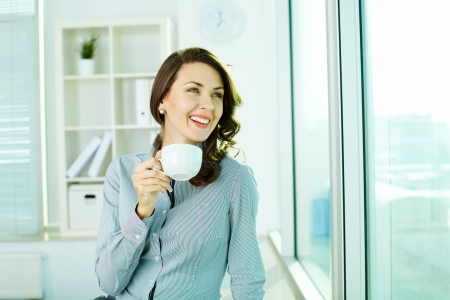 Cheerful woman with cup looking in the window at office photo