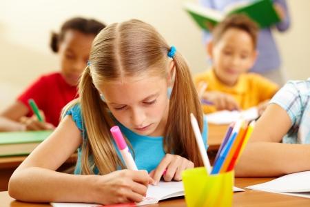 escuela primaria: Retrato de dibujo niña encantadora con lápices de colores en la lección