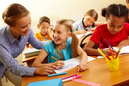 profesor alumno: Retrato de ni�a inteligente y su maestra buscando el uno al otro en la lecci�n en el aula