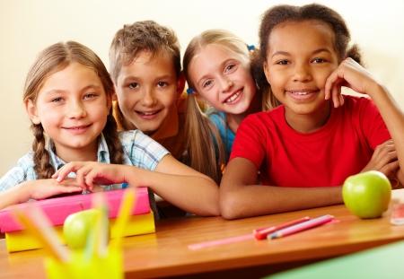 niños en la escuela: Retrato de los escolares inteligentes mirando a la cámara en el aula Foto de archivo