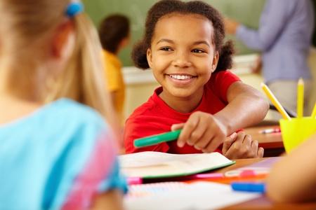 niños dibujando: Retrato de niña linda dando crayón para compañera de clase en la lección Foto de archivo
