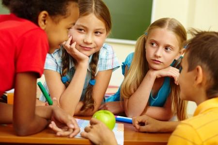 children talking: Portrait of friendly schoolchildren chatting in classroom