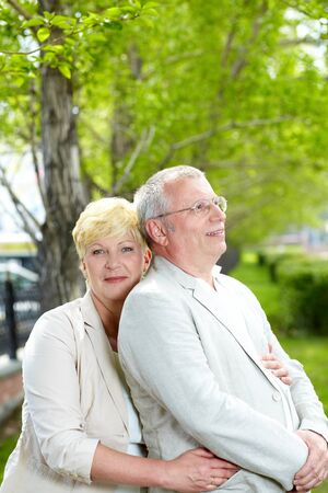 Mature woman looking at camera while embracing her husband outside Stock Photo - 13654023