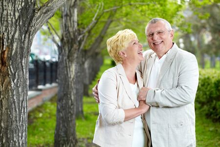 an elderly couple: Happy mature woman looking at her husband while having rest outside Stock Photo