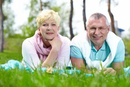 Happy mature couple lying on grass and having rest in summer photo