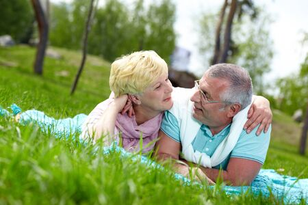 Happy mature couple lying on grass and looking at each other in the countryside photo
