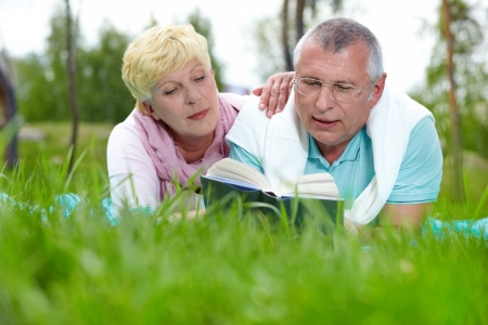 Happy mature couple lying on grass and reading a book in the countryside photo