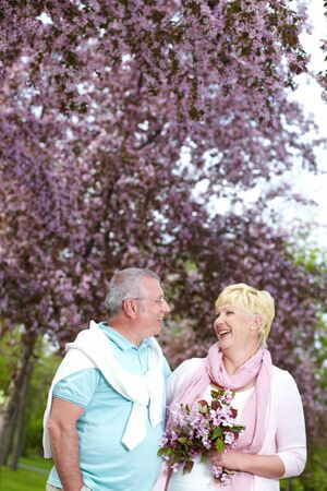 Happy mature couple looking at one another in blooming garden Stock Photo - 13653923