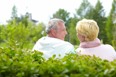 Mature couple sitting and talking in park in summer photo