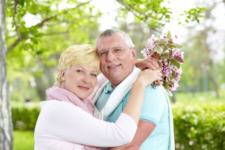 Happy mature couple embracing and looking at camera outside photo