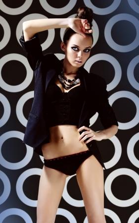 Gorgeous woman in black clothes posing on retro background Stock Photo - 13729491