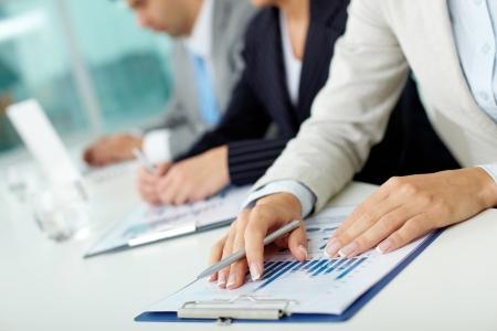 Close-up de las manos femeninas con la pluma sobre el documento de negocios en el entorno de trabajo
