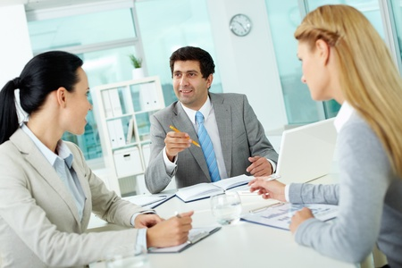 Confident businessman explaining his ideas to employees at meeting  photo