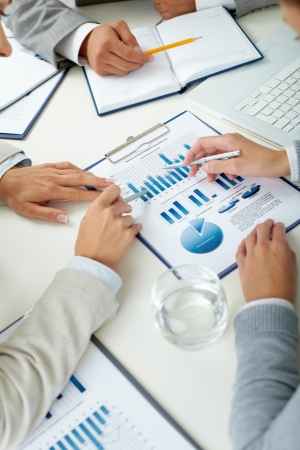 financial planning: Image of human hands with pens over business document at meeting Stock Photo