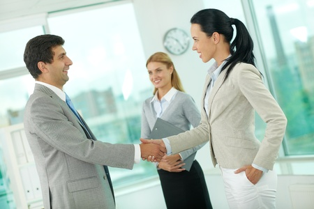 Portrait of successful associates handshaking after striking deal photo