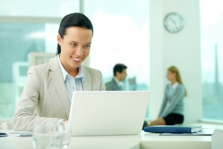Portrait of pretty secretary looking at laptop screen while typing Stock Photo - 13729494