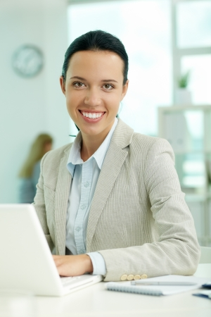 Portrait of pretty secretary looking at camera while working photo