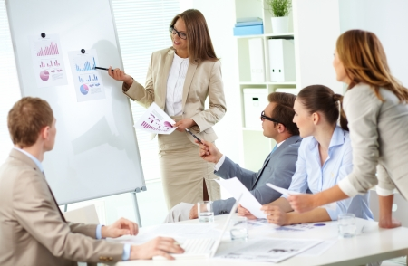 Confident businesswoman explaining her ideas to colleagues at meeting Stock Photo - 13729488