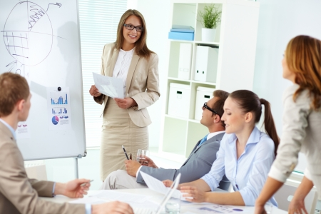 Confident top manager standing by the whiteboard and making report at meeting photo