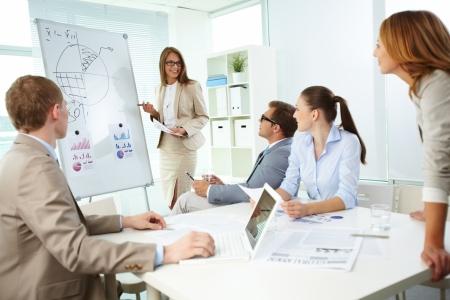 Confident top manager in piedi accanto alla lavagna e spiega la sua strategia a soddisfare