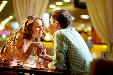 intimacy: A young happy woman and her boyfriend looking at one another in restaurant
