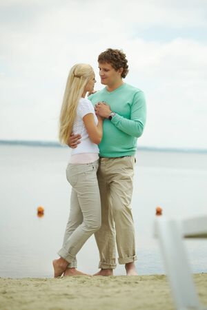 Image of handsome man and happy female embracing each other by the river or lake photo