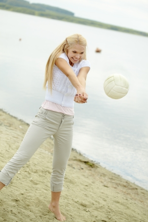 Photo of joyful blond woman playing volleyball photo