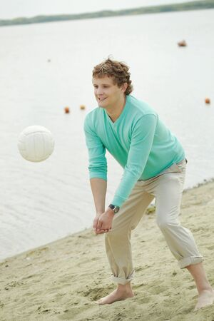 Photo of handsome man playing volleyball on the beach photo