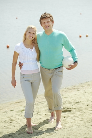 Image of handsome man and happy female walking down the beach photo