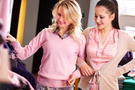 Image of two pretty girls looking at new clothes in department store photo