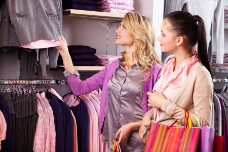 Image of two pretty girls looking at new collection of clothes in department store Stock Photo - 13729585