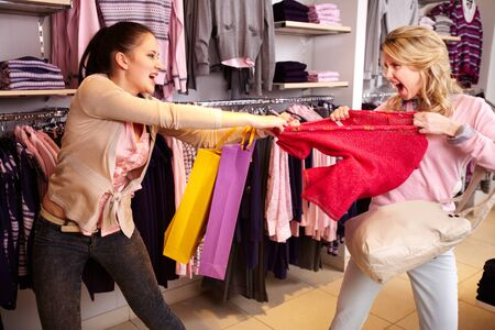 aggressive people: Image of two greedy girls fighting for red tanktop in department store Stock Photo